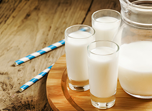 Jug of milk on old wooden table in rustic style, selective focus